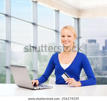 online shopping, banking, business and people concept - happy businesswoman with laptop and credit card over office window background - stock photo