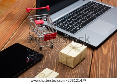 Online shopping concept - Empty Shopping Cart, laptop and tablet pc, gift box on rustic wooden background - stock photo