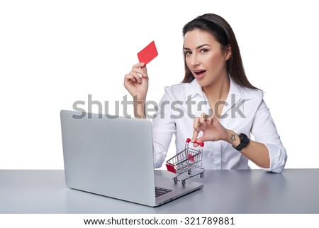 Online shopping concept. Playful business woman sitting at table with laptop with small empty shopping cart standing on table, holding empty credit card, isolated on white background - stock photo