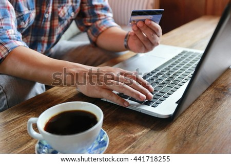 Online shopping.Hands holding credit card and using laptop. hand typing keyboard and use credit card with laptop shopping online,personal loans,businessman hand busy using laptop and coffee at office - stock photo