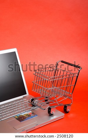 Online shopping. Shopping card and laptop, copy space.