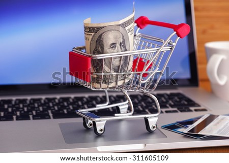 Online shopping. Shopping cart with one hundred dollars bill on laptop. - stock photo
