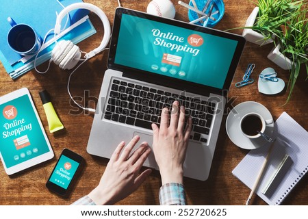 Online shopping website on laptop screen with female hands typing - stock photo