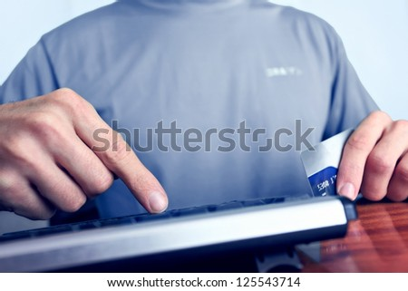 Online shopping with credit card, man makes an order by clicking the key on keyboard