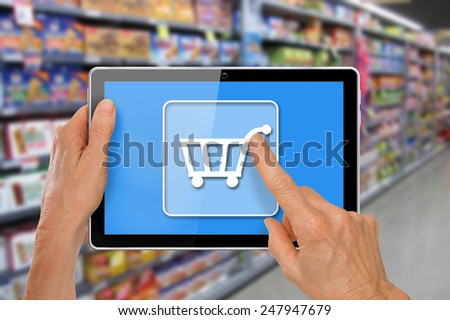 Online Supermarket Shopping Hands with computer tablet touching shopping cart icon in front of supermarket groceries  - stock photo