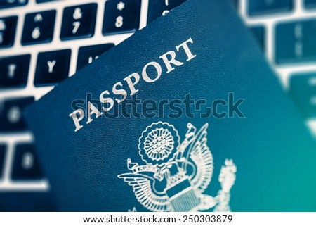 Online Travel Planning Concept Photo. United States of America Passport on the Computer Keyboard Closeup Photo. - stock photo