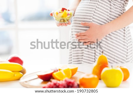 Only fresh and healthy food for my baby. Cropped image of pregnant woman holding a plate wirh fruit salad - stock photo