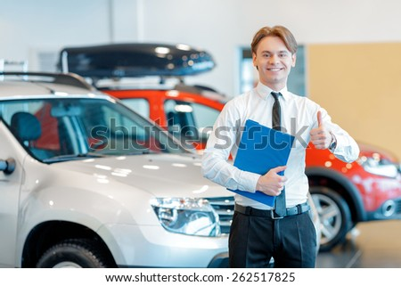 Only perfect cars. Young smiling salesman standing with a clipboard in his hands and showing his thumb up in car dealership - stock photo