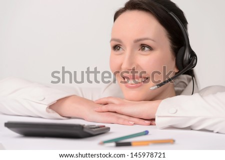 Only positive emotions. Portrait of beautiful middle-aged customer service representative leaning on the table and smiling with a calculator on the foreground - stock photo