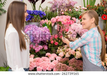 Only the freshest flowers. Young smiling florist showing flowers to the customer at the flower store - stock photo