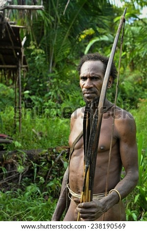 ONNI VILLAGE, NEW GUINEA, INDONESIA - JUNE 23: The Portrait Korowai man hunter with arrow and bow. Tribe of Korowai (Kombai , Kolufo).On June 23, 2012 in Onni Village, New Guinea, Indonesia