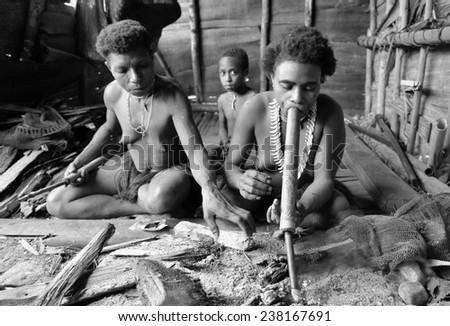 ONNI VILLAGE, NEW GUINEA, INDONESIA - JUNE 24: The Portrait of a Koroway woman smoking in the house on the tree. Korowai Kombai ( Kolufo).On June 24, 2012 in Onni Village, New Guinea, Indonesia  - stock photo