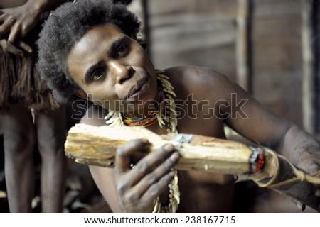 ONNI VILLAGE, NEW GUINEA, INDONESIA - JUNY 24: The Portrait of a Koroway woman smoking in the house on the tree. Korowai Kombai ( Kolufo).On June 24, 2012 in Onni Village, New Guinea, Indonesia  - stock photo