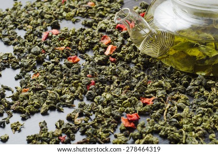 Oolong green tea with dried strawberries wooden table with teapot - stock photo