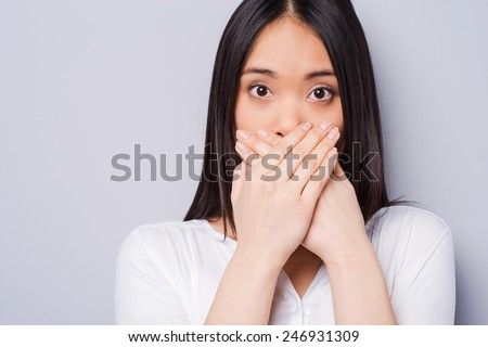 Oops! Surprised young Asian woman covering mouth with hands and staring at camera while standing against grey background - stock photo