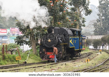 OOTY, INDIA - DECEMBER 30 :historic old vintage steam engine locomotive train moving down railroad track Nilgiri Mountain Railway December 30, 2014. Man standing in front of train Ooty India. - stock photo