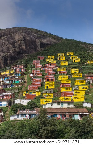 Ooty, India - October 25, 2013: Valparai village looks like a favela built on the slope of a hill. Bright yellow and wine red houses for poor people sponsored and painted by Idea and Vodaphone.