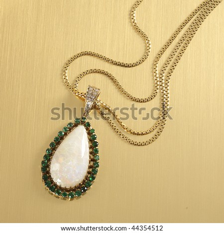 Opal pendant necklace with emerald and diamond accents on gold surface - stock photo