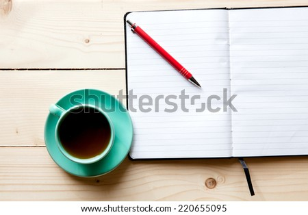 Open a blank white notebook, pen and cup of tea on the desk - stock photo