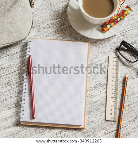 Open a blank white notebook, pen, women's bag, ruler, pencil and cup of coffee on the white desk - stock photo