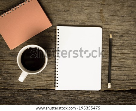 Open a blank white notebook, pencil and cup of coffee on the table - stock photo