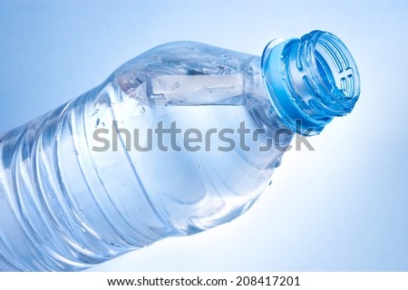 Open a bottle of water on blue background - stock photo