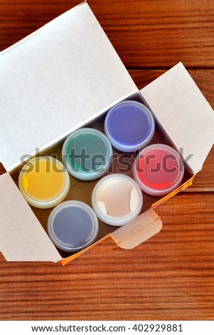 Open a box of colorful gouache on brown wooden background - stock photo