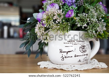 Open air coffee shop with flowers in vase on wooden table with shade from morning sun