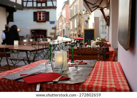 Open air street cafe or restaurant in the medieval Petite-France district at twilight - France, Alsace region, Strasbourg - stock photo