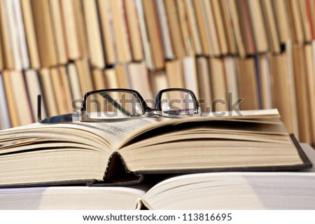 open and closed books and black glasses on  table front of a full bookshelf September 1st - the day of knowledge symbol of vision loss and eye strain from long reading  - stock photo