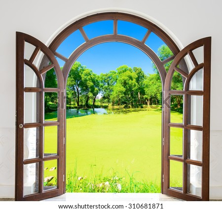 open arch door with a view of the pond - stock photo