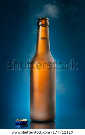 Open beer bottle on blue background - stock photo