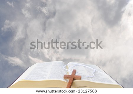 open bible against the clouds with a wooden cross on it - stock photo