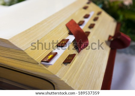 Open Bible on the altar in catholic church. Detail. Shallow DOF - stock photo