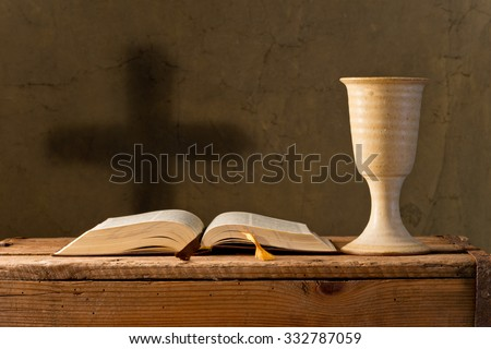 open bible with chalice of wine in the church - stock photo