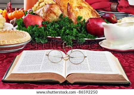 Open Bible with glasses lying on a holiday dinner table with prepared turkey and fixings in background. - stock photo