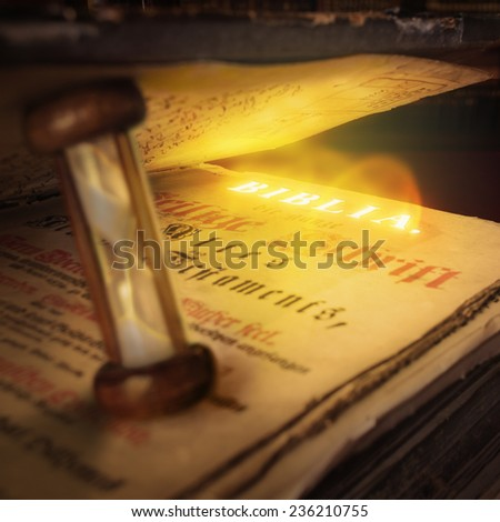 Open Bible with hourglass between the pages - square composition - stock photo