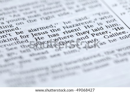 "Open Bible with selective focus on the text in Mark 16:6 about Jesus' resurrection: ""He has risen!"". Shallow DOF - stock photo"