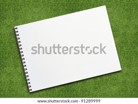 open binder notebook on grassland with empty page. - stock photo