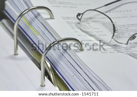 open binder with invoice and office items - stock photo