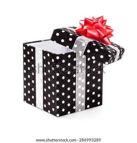 Open black gift box with white dots and red ribbon bow. Holiday present. Object isolated on white background. Clipping path - stock photo