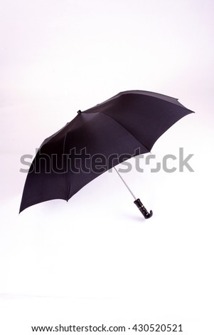 Open black umbrella isolated on white - stock photo