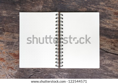 Open blank note book on grunge wood - stock photo