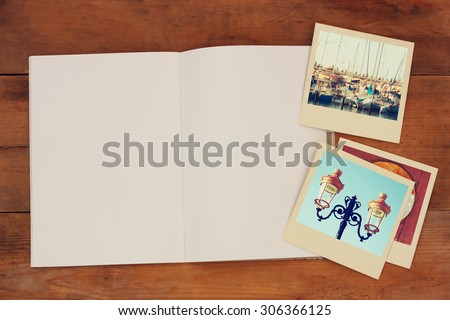 open blank notebook and old travel polaroid photographs over wooden table. ready for mockup. retro filtered image  - stock photo