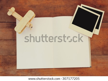 open blank notebook, wooden airplane toy and blank polaroid photography frames over wooden table. ready for mockup. retro filtered image  - stock photo