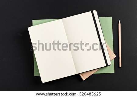 Open blank notepad with empty white pages laying above book with pencil on black background. ideal for text - stock photo