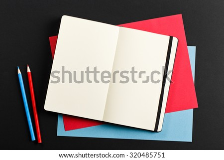 Open blank notepad with empty white pages laying with color paper and color pencils on black background. ideal for text - stock photo