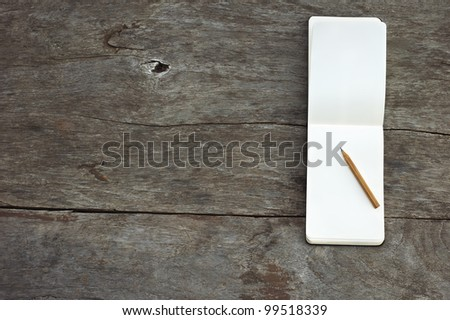 Open blank notepad with empty white pages with a pencil laying on a wooden table horizontal - stock photo