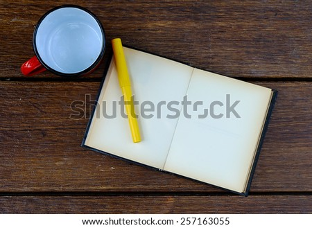 open blank old notebook on wooden table with empty red cup and yellow pen - stock photo