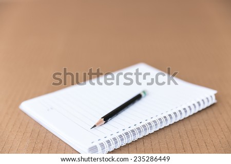 open blank pages of notebook with pencil